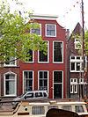foto van De Tol, pand met afgeknotte en van lijst voorziene klokgevel met hoekvoluten op geprofileerde dekplaten (XVIII). Hardstenen vensterdorpels. Ramen zolderverdieping