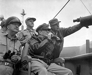 MacArthur wears a bomber jacket and his distinctive cap and holds a pair of binoculars. Almond is pointing something out to him.