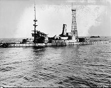 A stripped version of Indiana without gun barrels. The superstructure is seriously damaged and her stacks lean sideways, the front one pointing almost horizontal. A second wreck is visible in the background