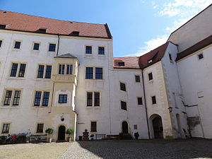 "Oflag IV-C - The inner courtyard of Colditz castle which was used as the prison yard when the castle was the POW camp Oflag IV-C during World War II. The door flanked by bushes was the entrance to the ""Prominente"" quarters. Note the cutout depiction of Lieutenant Bouley to the lower left hand side of the photograph."