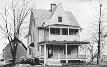 Casa de campo de 2 pisos de finales del siglo XIX con porches y un granero al fondo