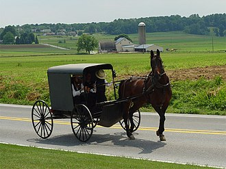 Amish - An Amish family riding in a traditional Amish buggy in Lancaster County, Pennsylvania