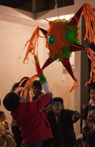 Las Posadas - Children in Oaxaca, Mexico celebrating Las Posadas by breaking a traditional star-shaped Piñata.