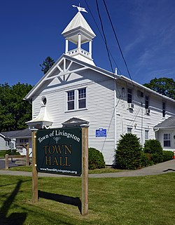 """A white wooden church-like building seen from its front left under a blue sky with streaky clouds. In front a large green wooden sign says """"Livingston Town Hall"""""""