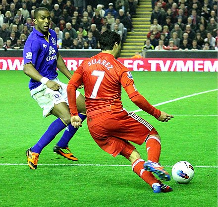 Suarez in action for Liverpool takes on Sylvain Distin of Everton during the Merseyside Derby in 2012 Luis Suarez runs at Distin 3.jpg
