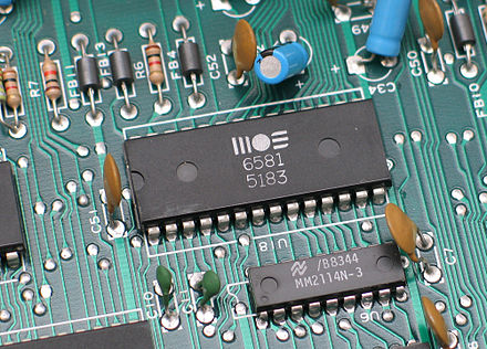 Through-hole devices mounted on the circuit board of a mid-1980s home computer. Axial-lead devices are at upper left, while blue radial-lead capacitors are at upper right MOS6581 chtaube061229.jpg