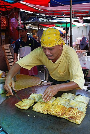 Murtabak - A street side cook making murtabak on top of large flat fry pan