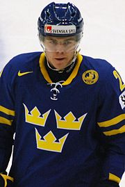 An ice hockey player standing directly in front of the camera. He is wearing a blue helmet with a visor and a yellow and blue uniform.