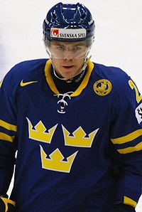 An ice hockey player standing, facing towards the camera. He is wearing a blue helmet and a blue and yellow uniform.