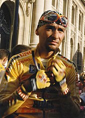 A cyclist unzipping his yellow cycling jersey.