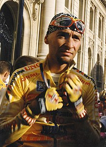 A cyclist wearing a yellow jersey while in the process of unzipping his jersey.