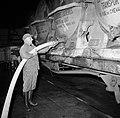 Melkfabriek man assisteert bij het tappen van de melk uit de wagons, Bestanddeelnr 252-9442.jpg