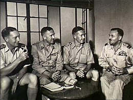 A group of four senior military officers sitting down together conversing. There is a small table in front of them with a book on it.