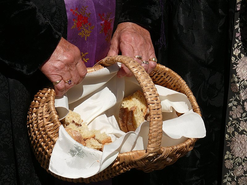 Distribution of holy bread at a mass exit in Montgellafrey (Savoie, Rhône-Alpes, France).