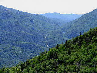 NY 73 is a state highway located entirely within Essex County. The highway begins at an intersection with NY 86 in the village of Lake Placid and ends at a junction with U.S. Route 9 north of the hamlet of Underwood. NY 73 meanders through mountainous regions of Adirondack Park, such as Keene Valley (pictured above).