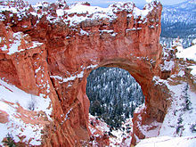 A large opening in red rock with snow on top
