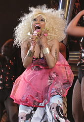 A blonde Afro-American woman dressed in a gauzy pink costume while singing and looking upward. Smiling, her wrists bear gold bangles and there is a lip-shaped ring on her finger.