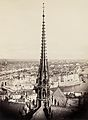 Notre Dame, Paris, France. View of spire, roof with statuary, and cityscape beyond.jpg