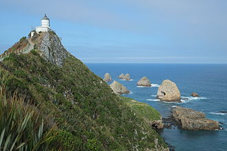 Nugget Point - View along path towards Nugget Point lighthouse. Rocky islets (The Nuggets) can be seen beyond the lighthouse.