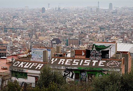 "The famous okupas squat near Parc Güell, overlooking Barcelona (on the roof: ""Occupy and Resist""), since squatting was a prominent part of the emergence of renewed anarchist movement from the counterculture of the 1960s and 1970s ParcGuellOkupas.jpg"