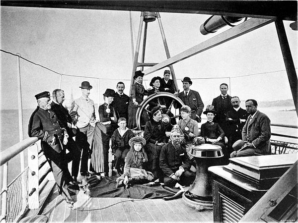 Black and white photograph of a group of men and women posing on the desk of a steamship.