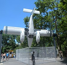 A Seneca pivoting around its wing spar and pointing vertically downwards, installed around 4 meters above a pavement in a park, with people walking underneath