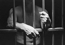 Black and white photograph of a man behind bars