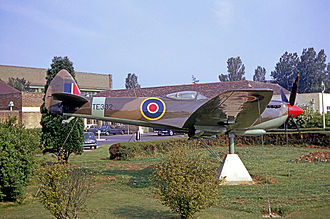 Cotswold Airport - The RAF Kemble main entrance area in 1967 with a pre-war hangar in the left background and a Spitfire as gate guardian