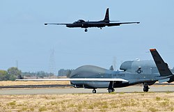 An RQ-4 Global Hawk taxies on the flight-line as a U-2 Dragon Lady makes its final approach at Beale Air Force Base during 2013.