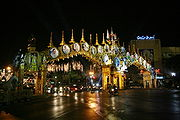 An elaborate double archway above a road, with pictures of King Bhumibol Adulyadej; trees decorated with lights