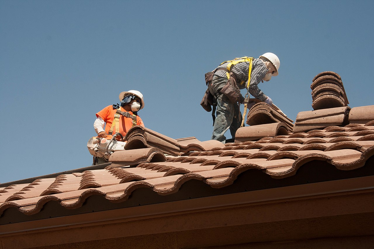 Roofers using fall-arrest equipment. They are roofing.