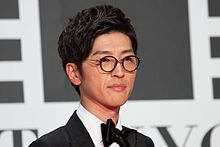 A short black haired Japanese man wearing glasses and black clothes.