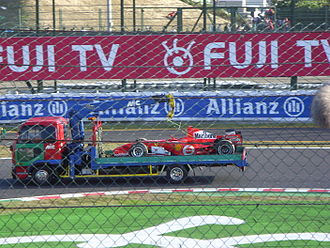 2006 Japanese Grand Prix - Michael Schumacher's Ferrari is returned to the pits after an engine failure cost him the race lead, and handed Fernando Alonso a ten-point advantage in the Drivers' Championship with one race remaining.