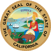 "Circular seal surrounded by ""THE GREAT SEAL OF THE STATE OF CALIFORNIA"", with ""EUREKA"" atop the central image. A seated woman wearing ancient Roman warrior dress, with a shield at her feet, a spear in one hand, and a crested centurion's helmet, looks over a bay with four sailing ships. A small brown bear at her feet noses at vegetation. A miner in the near distance swings a pickaxe into the dirt near a shovel, pan, and sluice. Tall mountains line the bay, and 31 stars arc through the sky."