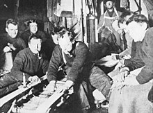 A group of men in woollen jerseys, several smoking pipes, are watching repair work on a sledge. They are in a confined area, with equipment and spare clothing adorning the walls