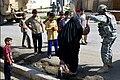 Soldier helps an elderly Iraqi woman cross a curb.jpg