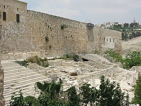 The long southern wall of Jerusalem's Temple Mount rises above two flights of stone steps between which are some low ruins