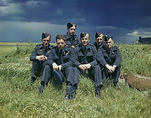 The crew of Lancaster AJ-T sitting on the grass, posed under stormy clouds.jpg