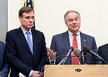 Two older white men in suits stand behind a podium while one talks.