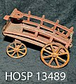 Toy figure of a red metal farm wagon with yellow wheels; flat bed bent to form front of wagon, curved side rails, small front (b0ed11d1-75a0-40b1-ba7c-0eede871838b).jpg