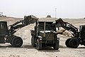 Two U.S. Marine Corps tractors dump sand into a medium tactical vehicle replacement at Camp Bastion, Helmand province, Afghanistan, Aug. 7, 2013 130807-M-SA716-113.jpg