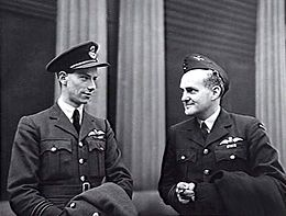 Informal half portrait of two men in dark military uniforms with pilot's wings on the left pockets