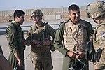 USAF Lt. Col. Blaine Baker speaks with pilot of Iraqi air force C-130J Super Hercules after landing at Qayyarah West.jpg