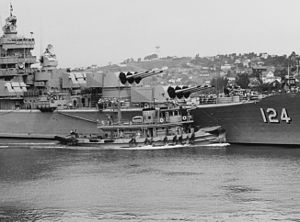 USS Awatobi (YTB-264) assists USS Rochester (CA-124) in departing Mare Island Naval Shipyard on 20 September 1953 (NH 84584).jpg