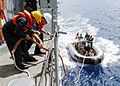 US Navy 030605-N-7902K-116 Boatswain's Mate 1st Class Patrick Stewart and Boatswain's Mate 3rd Class Jeff Comer secure the forward steadying line while retrieving the rigid hull inflatable boat (RHIB).jpg