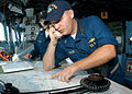 US Navy 030830-N-8955H-008 Lt. j.g. Shawn Trisler, from Austin, Texas, checks a navigation chart in the amphibious command ship USS Blue Ridge (LCC 19) pilot house while conversing with the ship's Combat Information Center.jpg
