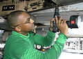 US Navy 040731-N-4565G-002 Aviation Structural Mechanic 2nd Class Kelvin Santos of Bronx, New York replaces rivets on the tail hook hydraulic system of an F-A-18B Hornet.jpg