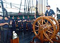 US Navy 050823-N-9076B-001 Electrician's Mate 1st Class Aaron Walker speaks to chief petty officer selectees as he stands at the helm of USS Constitution in Boston.jpg