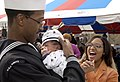 US Navy 051108-N-4776G-088 Aviation Boatswain's Mate Seaman Joseph Kincannon is greeted excitedly by his wife as he holds his son for the first time after arriving home in San Diego.jpg