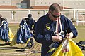 US Navy 060315-N-3271W-002 U.S. Navy Parachute Team Leap Frogs crew member, Chief Engineman Dave Casper repacks his gear after a jump at the Willow Canyon High School, during Phoenix Navy Week festivities.jpg